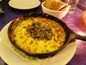 """""""Queso fundido"""": queso chihuahua, semillas de calabaza tostadas caramelizadas y chile de árbol. Servidas con tortitas tipo nachos."""